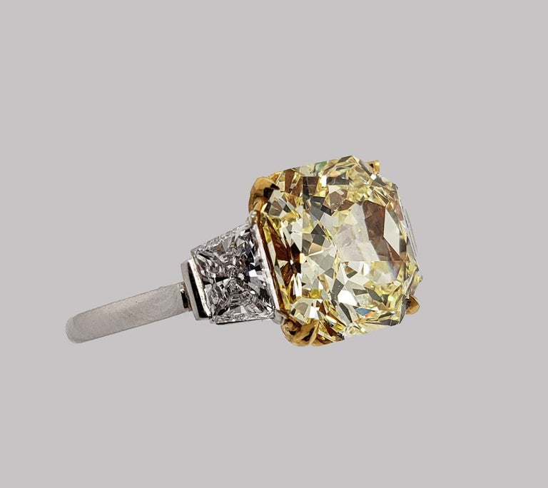 This SCARSELLI 4.01 carat Fancy Intense Yellow Radiant Cut Diamond Ring is  VVS2 clarity.   Flanking the center diamond are a pair of fine white brilliant cut trapezoid diamonds in platinum. The high quality of the diamonds and mounting are