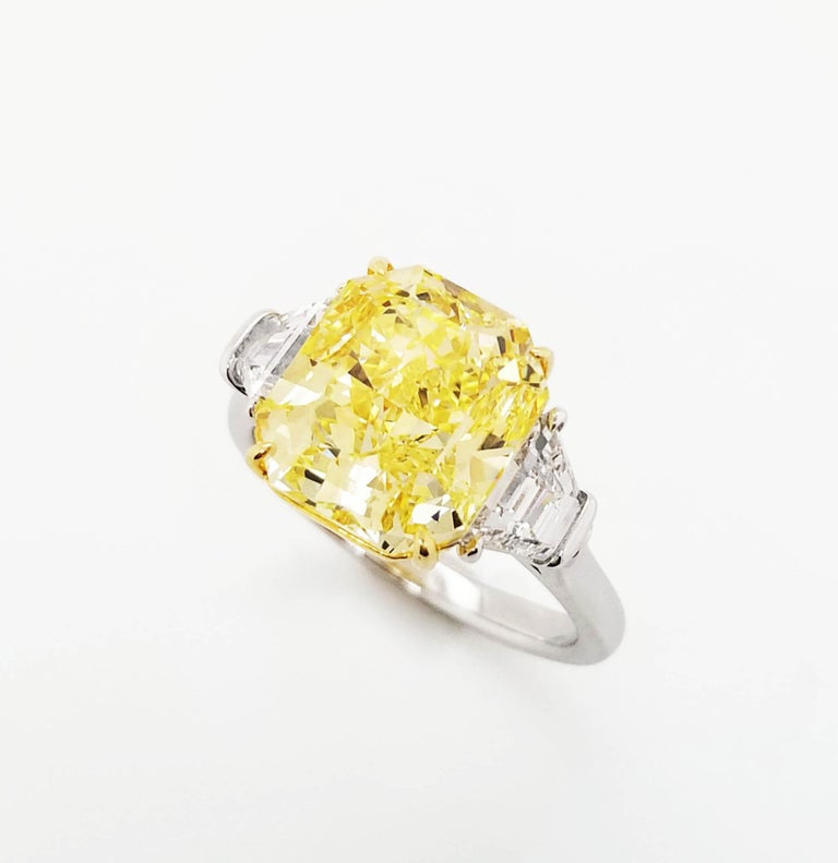 SCARSELLI is featuring a 5+ carat Fancy Intense Yellow Radiant Cut Diamond VS1 clarity, certified by GIA ( see certificate picture for detailed stone information) flanked by a pair of trapezoids VS diamonds totaling 0.92 carats set in handmade 18k