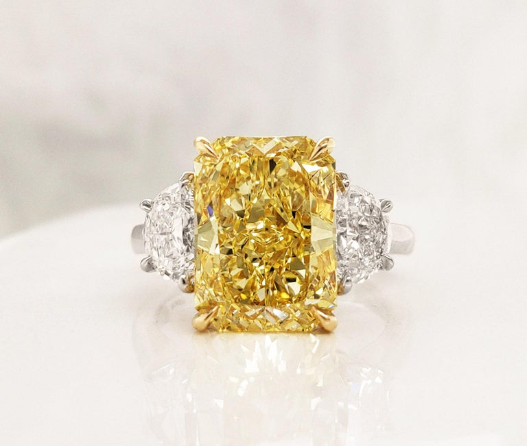 From SCARSELLI, this astonishing statement ring features a 5.01 carats Fancy Intense Yellow radiant cut diamond of VS2 clarity flanked with half-moon cut white diamonds 1.10 carats (0.55 each). Platinum and 18k yellow gold ring perfect for any