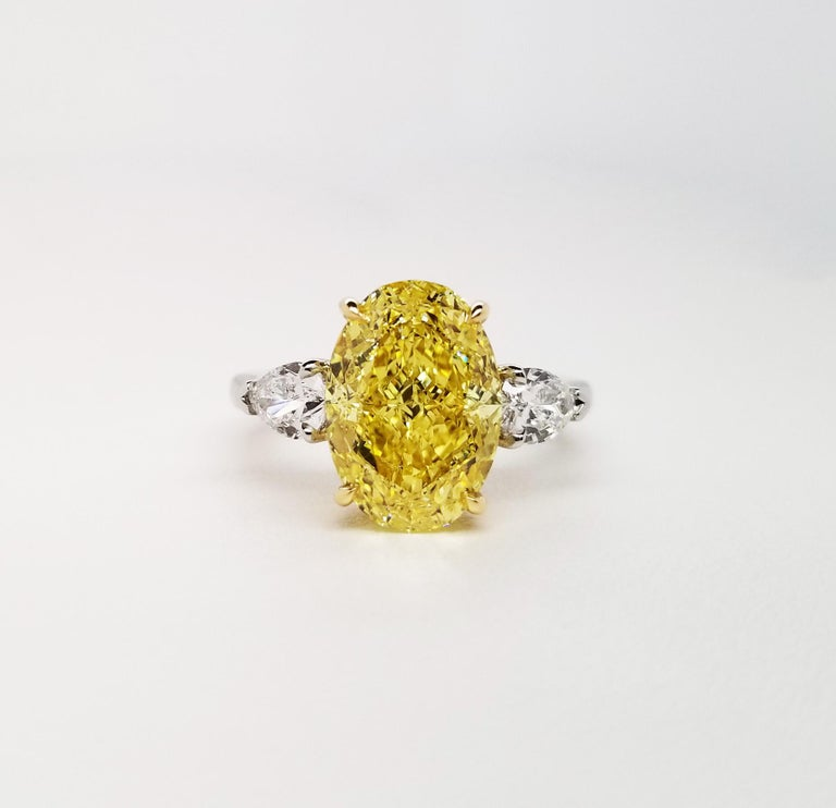 This Beautiful Classic engagement ring from Scarselli features an over 5 carat fancy vivid yellow oval cut diamond GIA certified (see certificate picture for more detailed stone's information) flanked by a couple of GIA certified pear-shaped E