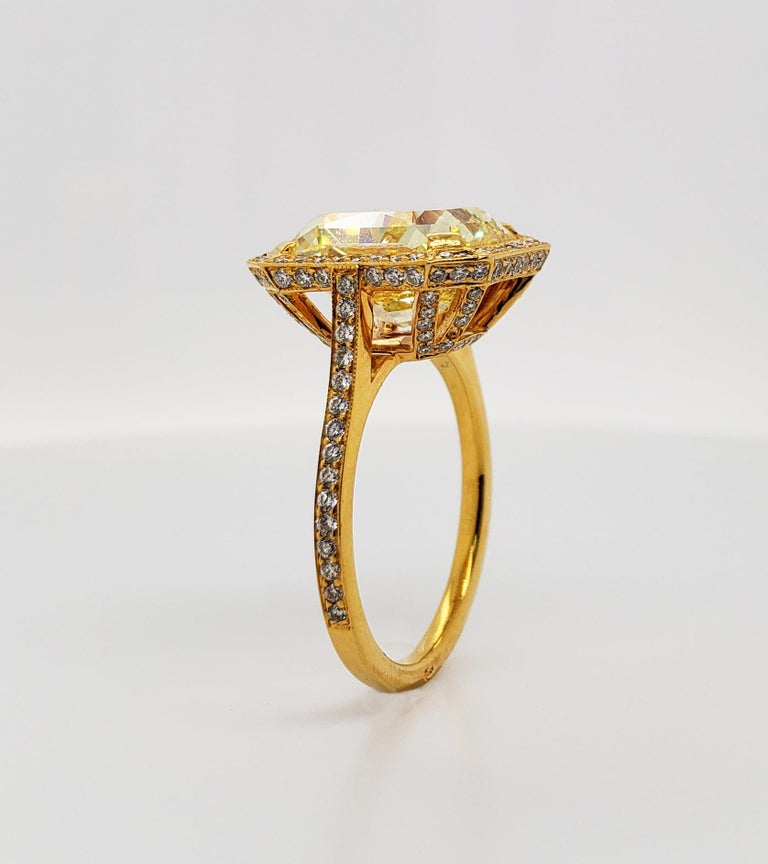 From SCARSELLI, a simply important ring featuring a 6.70 carat Fancy Vivid Yellow Radiant cut diamond (GIA VS2) surrounded by 0.44 carats of small white diamonds in a coordinating handmade mounting of 18 karat yellow gold. Vivid yellow diamonds of