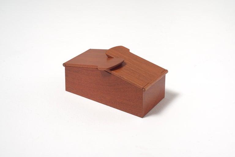 An elegant wooden box with architectural lines, whose lid is made of two parts that meet to complement each other in a delicate embrace.