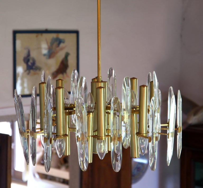 Twelve lights chandelier from Gaetano Sciolari, production made for Stilkronen, Italy, 1970s. Eight lights down and four lights up. Brass gold-plated. Transparent elements in Led Crystal. Bulbs are sorrounded by 24 led crystal vertical elements to