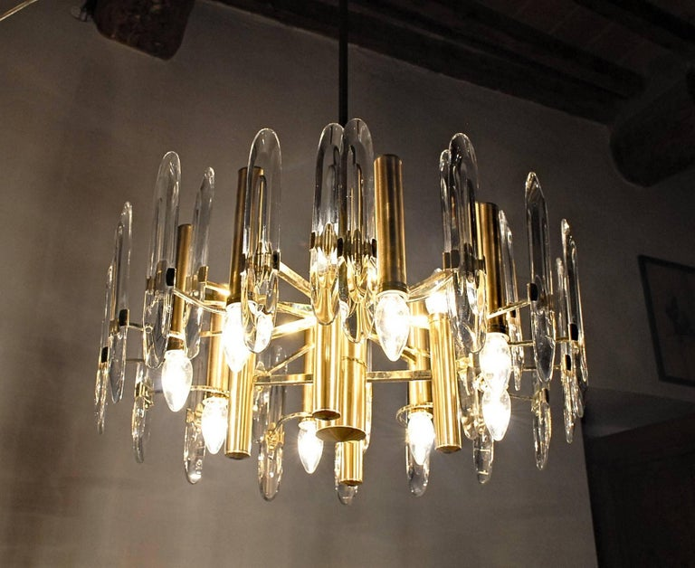 Twelve light chandelier from Gaetano Sciolari production made for Stilkronen, Italy, 1970s. Six lights down and six lights up. Brass gold-plated. Transparent elements in Led Crystal.  This is an interesting version of the Sciolari's production.