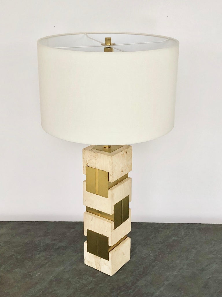 A large travertine marble and brass table lamp by Gaetano Sciolari. Retains the original square shade. The marble pieces interlock with the brass elements and create a look reminiscent of jewelry. Retains original square shade and finial. Signed on