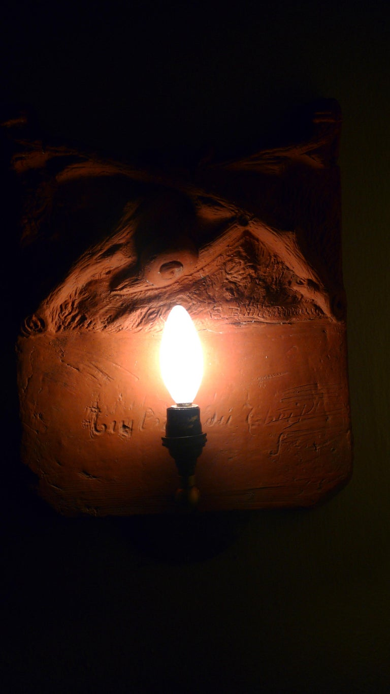 Early 1700s French terracotta garden stone signed by the artist. Has been made into a hallway sconce. Mysterious, earthen, tactile. Depicts snail crawling amongst ground cover. Professionally wired candelabra socket and bulb is hardwired into