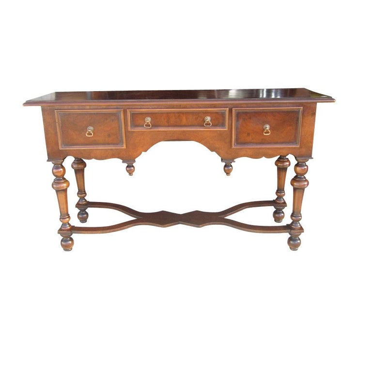 Burled walnut console table in the traditional style manufactured by Scott Thomas. This table features intricate brass pulls and nice detailing on the wood including turned legs and a finely carved leg support. Three small drawers.