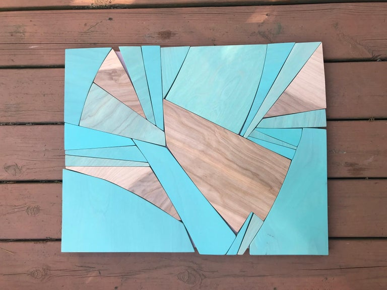 Coastal Span is a vibrant, bold, monochromatic wall sculpture made from acrylic washes, enamel and latex paints on Birch panels and MDF. The varying opacities of blue washed paint over the birch panels allow the brown wood grain to remain visible
