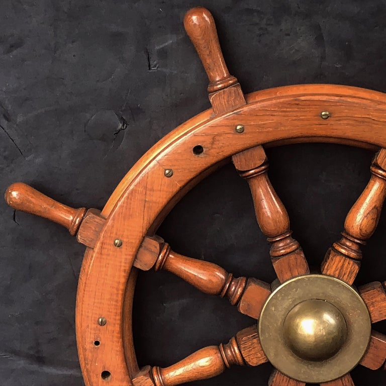 A fine Scottish ship's wheel of turned mahogany and brass, featuring an eight spoke wheel around a heavy brass hub.