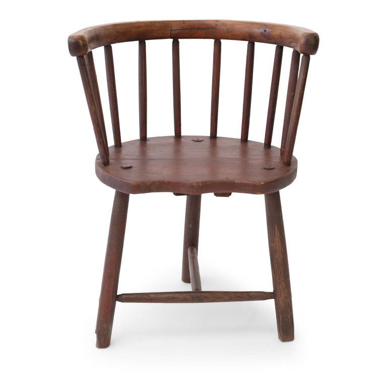 Scottish horseshoe-back chair, circa 1850-1870. This vernacular Windsor style stick-back chair from Argyll, Scotland, features pegged construction and remnants of original earthy red milk paint. Its seat is pine, legs and spindles are elm and the