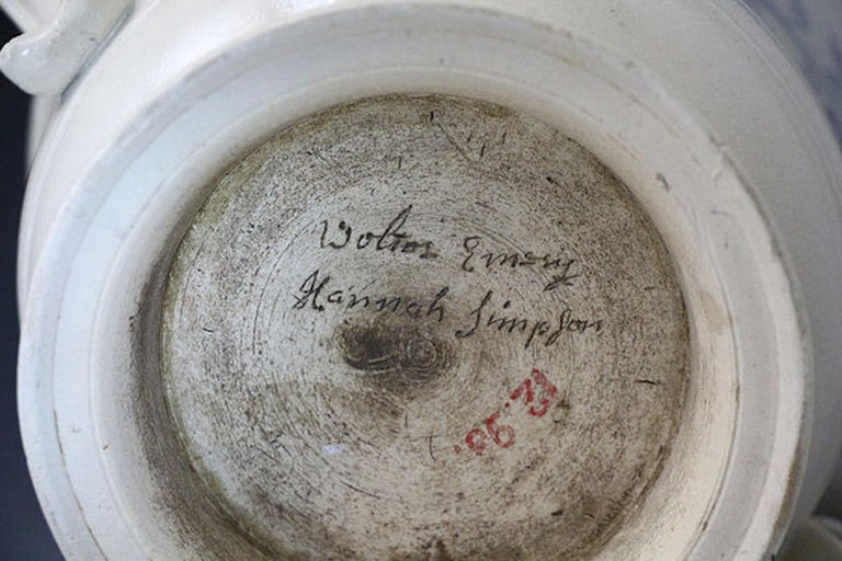 A rare scratch-blue decorated saltglaze loving cup with incised images of flowers and foliage. Made in Staffordshire in the mid-18th century. The unglazed underside of the base has an inscription in script with the names
