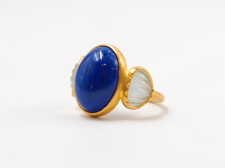 This delicate ring is composed of an intense lapis lazuli cabochon of 7.58 cts surrounded by 2 opaque aquamarines carved as shells. The lapis lazuli is natural with typical inclusions and shows the blue afghan colour.   This one-of-a-kind ring is