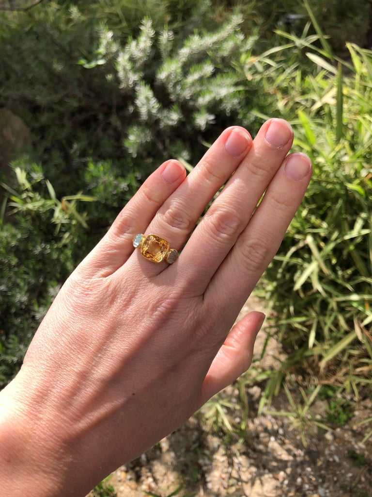 This delicate ring is composed of citrine facated of 4.53 cts surrounded by 2 aquamarines carved as shells (totale weight: 1.44cts). The stones show natural, typical and eye-visible inclusions.   This one-of-a-kind ring is handmade with 22kt mat