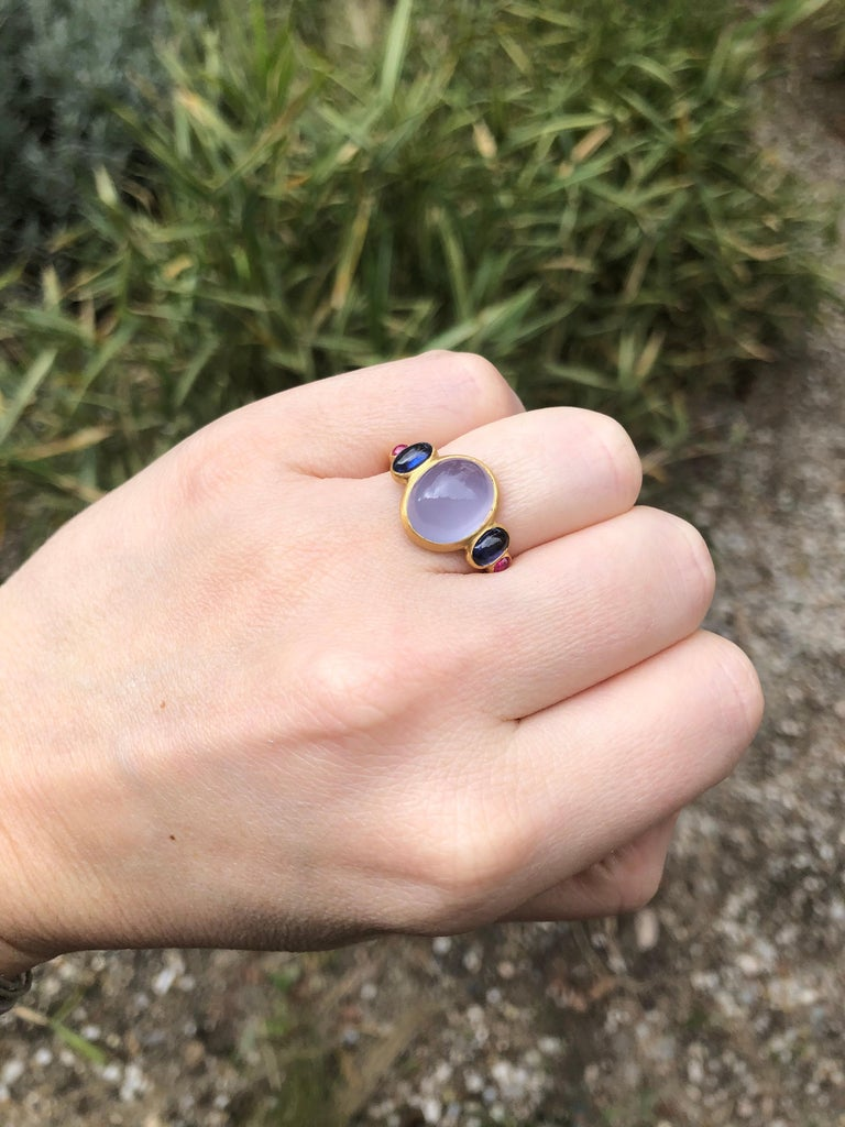 This delicate ring is composed of 5 stones in line: 1 Blue chalcedony cabochon, 2 blue kyanite cabochons and 2 rubies sugarloaf cabochons.  The center stone is a blue chalcedony of 5.27 cts. The kyanite total weight is 1.26cts. The 2 sugarloaf