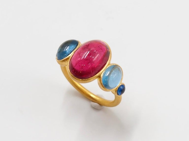 This delicate ring is composed of 5 stones in line: 1 deep red natural rubelite (red tourmaline) cabochon, 2 natural aquamarine cabochons and 2 blue sapphire cabochons. The center stone is an rubellite of 5.92 cts and the 2 aquamarines have a total