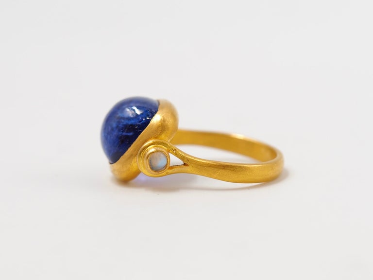 This antique style ring by Scrives is set with a purplish blue tanzanite sugarloaf cabochon of 6.46 cts. and 2 cabochon moonstones of 0.17cts on the side. The central stone and its setting are slightly turning/moving in order to give more comfort.