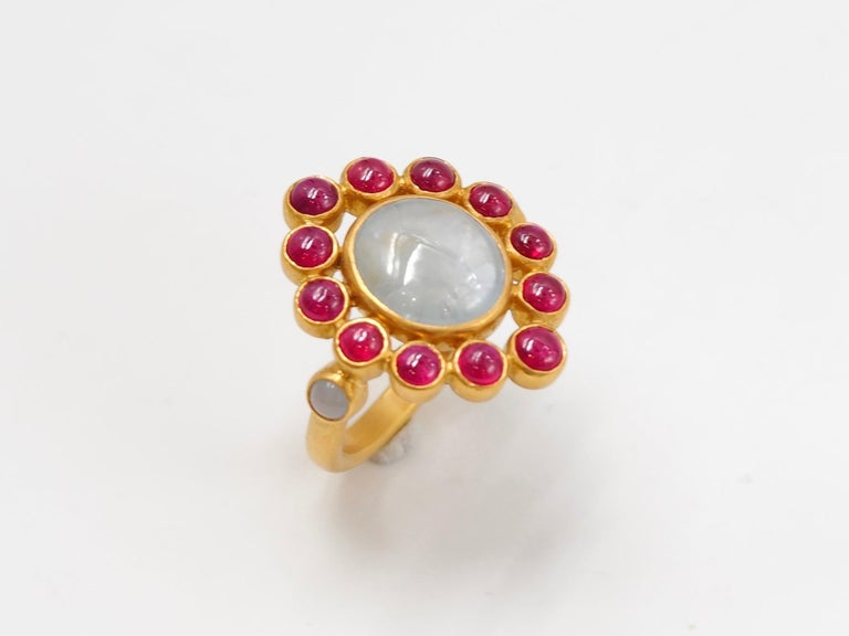 This one-of-a-kind ring by Scrives is composed at its centre of an oval grey sapphire cabochon of 6.7 carats natural & without treatment. The sapphire origin is Burma / Myanmar. It is surrounded by 12 round Rubies cabochons (total weight of rubies: