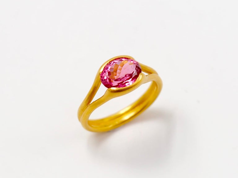 This delicate ring by Scrives is composed of an hot pink tourmaline of 2.38cts.   The stone is hold by 2 gold lines that form the band. This design allows light to come into the stone from multiple directions and put into highlight the stone.   The