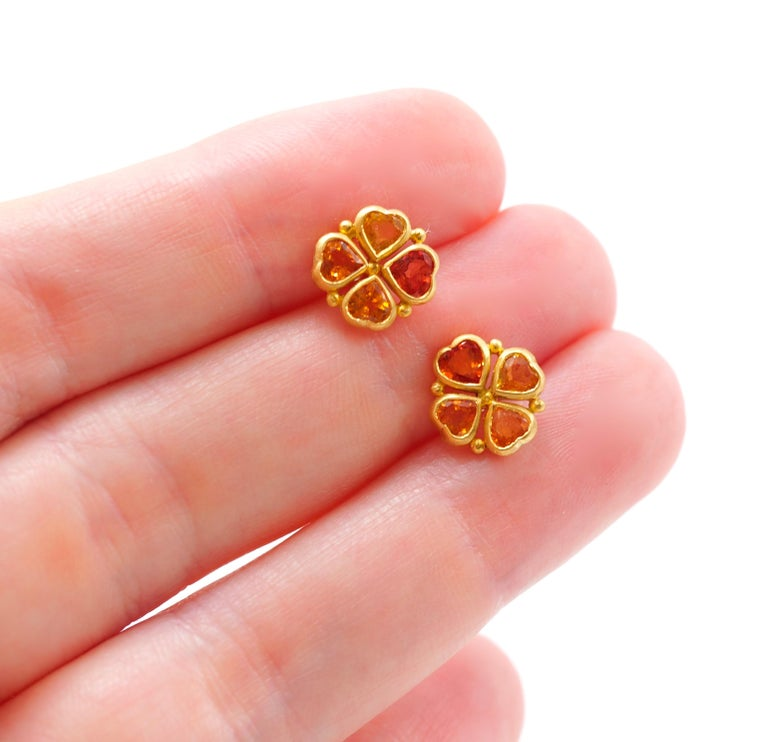 These earrings by Scrives are composed of 4 hearth shape sapphires (total weight of 1.38 cts). All 4 stones have different shapes and colours / hues from yellow to strong orange.   The stones are set in gold (closed setting) and in the gaps, a gold