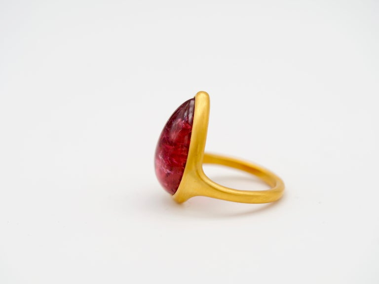 This modern ring by Scrives is composed of a large Pink/red tourmaline cabochon of 13.11cts set in 22kt gold. The tourmaline has very interesting natural inclusions some with darker red colour and others with shinny & rainbow effects which