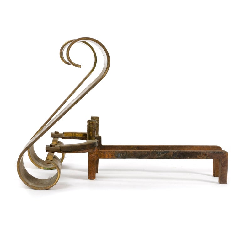 A pair of American brass Art Deco scroll andirons supported by iron arms. Stamped 'AWS' and 'Puritan'.
