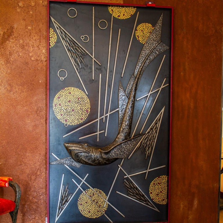 A remarkable and rare sculpted and cast metal panel by Michel Zadounaisky, depicting a silver patinated shark surrounded with shoals of fish and abstract metalworks. The whole panel is framed in red steel and signed and dated within the scene
