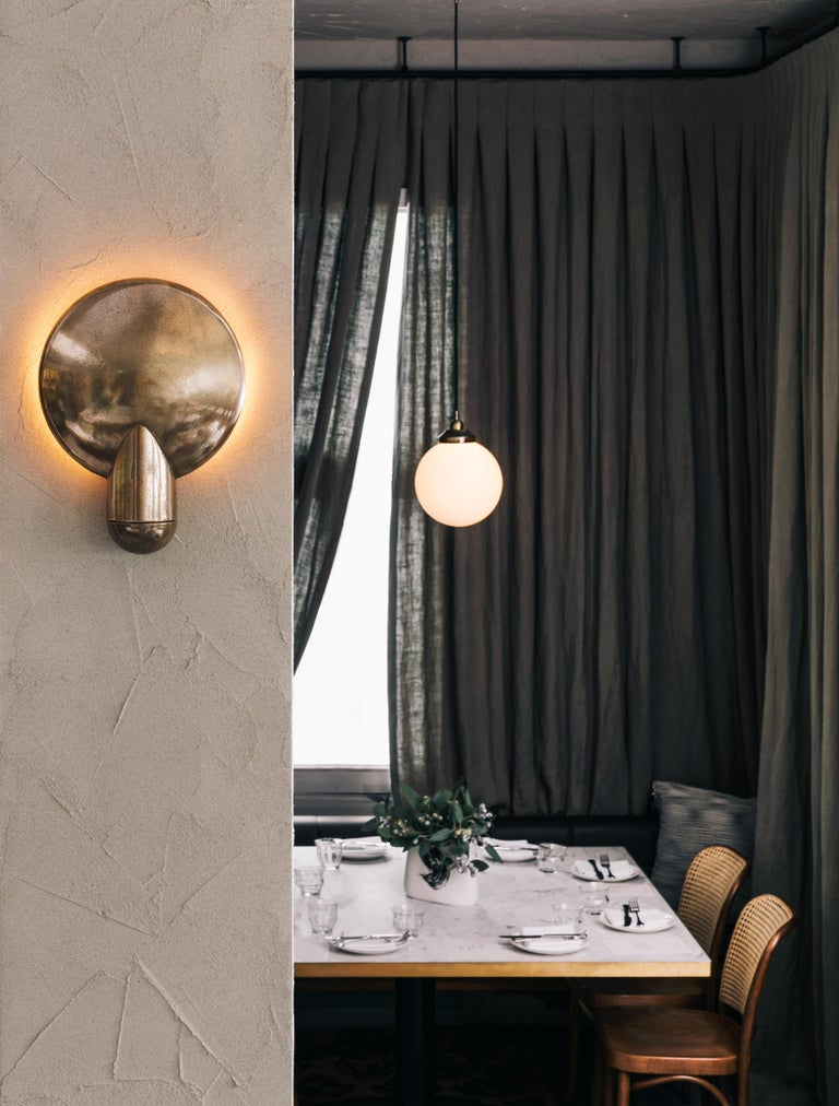 Sculpted bronze sconce light by Henry Wilson This sculptural item is handmade in Sydney, Australia. Sandwiched between the two bronze components, the light source is projected onto the concave backing. The light follows the gentle bowl of the dish