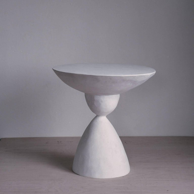 The Marasai side table is cast in a five part process and sculpted from concrete and plaster and sealed with lime. Because it is sculpted by hand in our studio, each form varies slightly in texture from the next.  Dimensions: 20