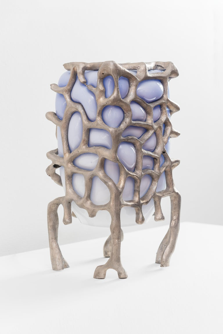 This eerie table lamp is a sculpture that will change the feeling of any room. Alive and glowing and iridescent. Pictured with a blue bulb the color is variable based on what bulb is used for the piece. Pictures here show the lavender color of the