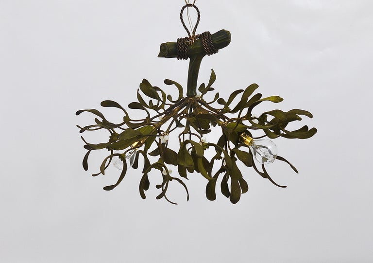 A beautiful French Art Nouveau mistletoe chandelier light fixture from the 1920s. Handmade of bronze, hand painted, the berries are made of opaline glass. The chandelier has three light sources. In very good condition.