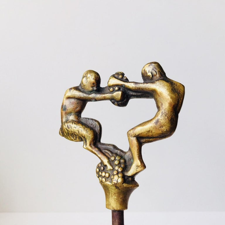 This vintage corkscrew in brass and steel was designed by Kay Bojesen in the early 1920s and manufactured by E. Dragsted in Copenhagen. The top of the corkscrew depicts a faun fighting a man over grapes.