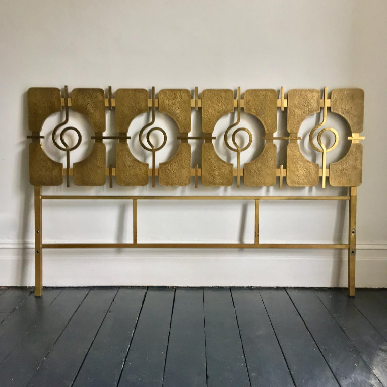 Striking sculptural headboard of cast brass on a gold-colored frame, designed by Luciano Frigerio, Italy, circa 1965.   This is a stylish, and heavy piece, in good original condition. The decorative section comprises panels and linking scrolls of