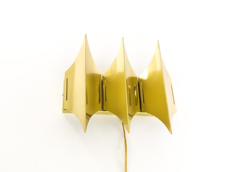 Sculptural wall lamp Gothic III produced by Danish lighting company Lyfa, with three-light sources. The lamp has been designed and manufactured halfway the 1960s. This lamp is made of brushed solid brass that accentuates the three horizontal