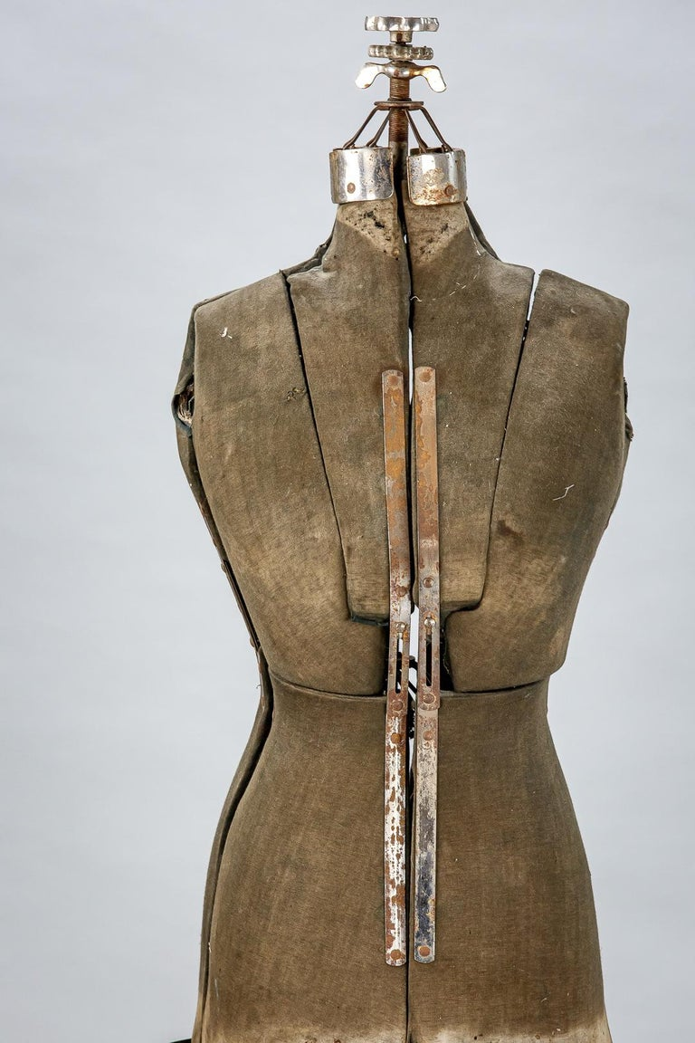 Early 20th century sculptural dressmakers mannequin, strap metal skirt and adaptable body mechanism. Original iron stand. France circa 1920. As expected wear and patination. Dimensions: 42cm x 172cm x 42cm.