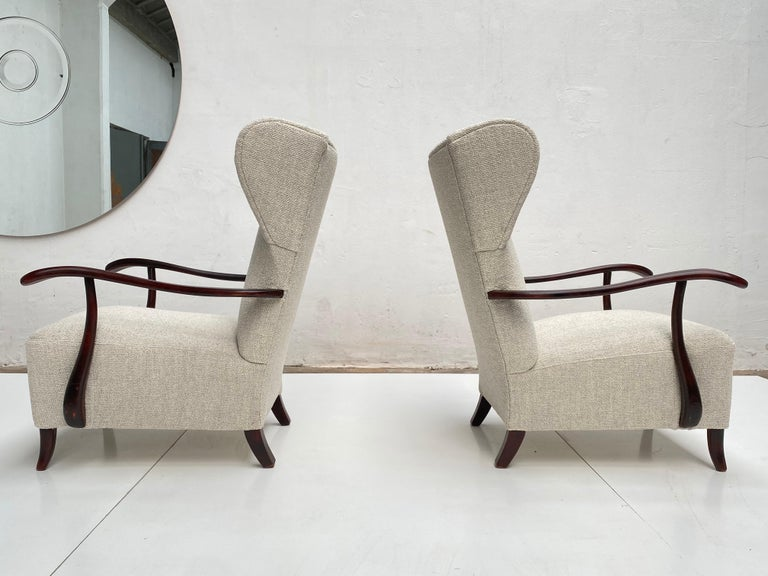 Lovely pair of 1940s sculptural form, wing back chairs attributed to the italian architect and designer Paolo Buffa who learned his trade in Gio Ponti's studio in the late 1920s. The chairs feature a beautiful flowing hardwood armrest design which