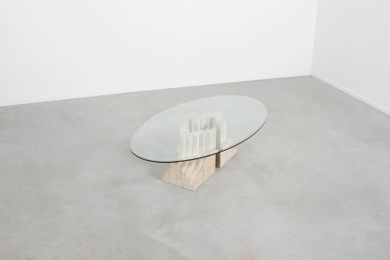 Sculptural coffee table in very good condition in the style of Tobia Scarpa  The table consists of two multi-layered travertine bases and an oval glass top.  The bases are made of 9 layers of stacked solid travertine slabs.