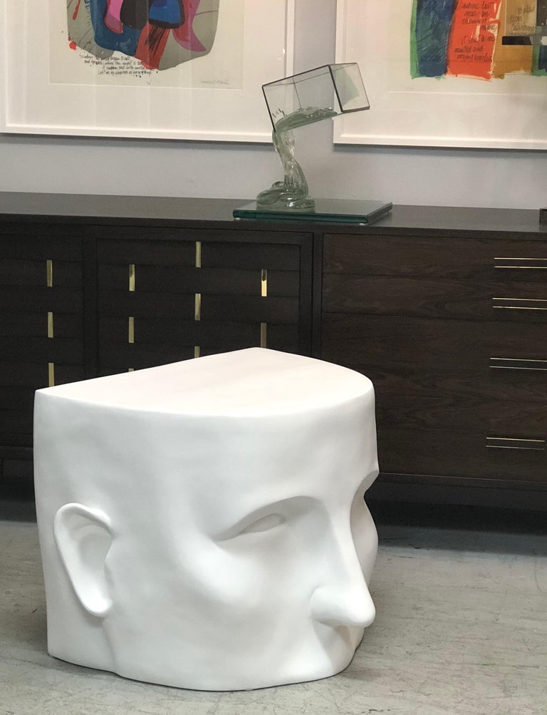 A large architectural table or bench in the form of an stylized partial head. It is resin with a white flat enamel finish, looks like plaster. 2 available.