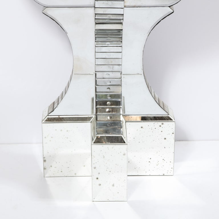 This stunning 1940s Art Deco Hollywood Regency console table features an antiqued mirror base from which three sculptural scalloped forms ascend. These forms offer a mosaic of reverse etched rectangular panels with spherical detailing on their