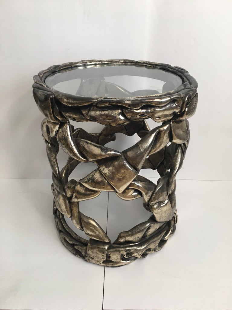 Delicious candy ribbon occasional side table in the Hollywood Regency style of Tony Duquette. Features Original silver leaf finish with natural patina showing gunmetal gray/aged chrome undertones. This sculptural Mid-Century Modern piece has a