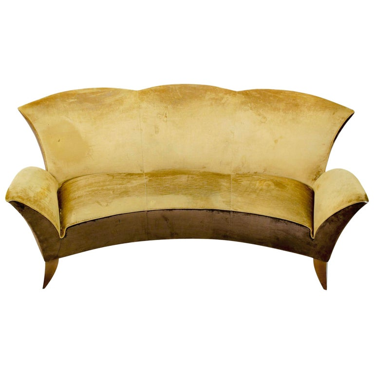 Sculptural Italian design sofa, circa 1960s. High curved back with scalloped detail for 3 seats and is upholstered to the floor. An impressive sofa from every angle. Looks to have been reupholstered in the 1970s. Front legs have been