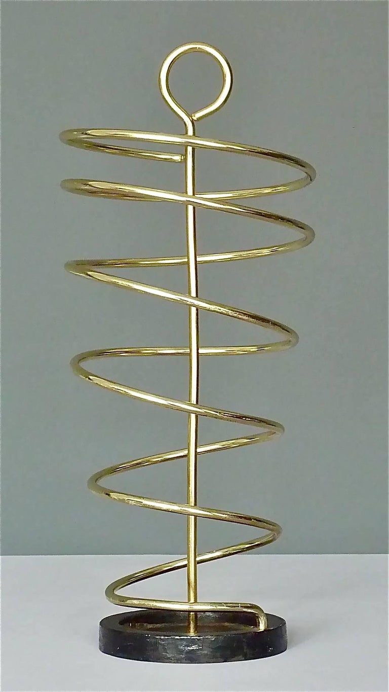 """Fantastic sculptural midcentury """"Spirale"""" umbrella stand designed and executed in the 1950´s in Italy. It is made of golden color anodized aluminum metal formed to an up-going spiral with handle and a black enameled iron base at the bottom for a"""