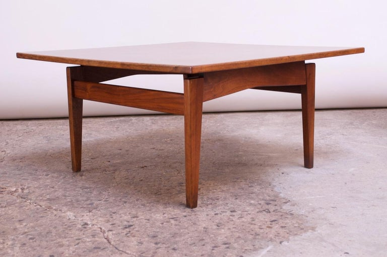 Early Jens Risom coffee table for Risom Design Inc. (circa late 1940s-early 1950s). Composed of a 'floating' laminate top supported by a sculpted walnut base. Walnut has been refinished, and the table, overall, is in very good, vintage condition