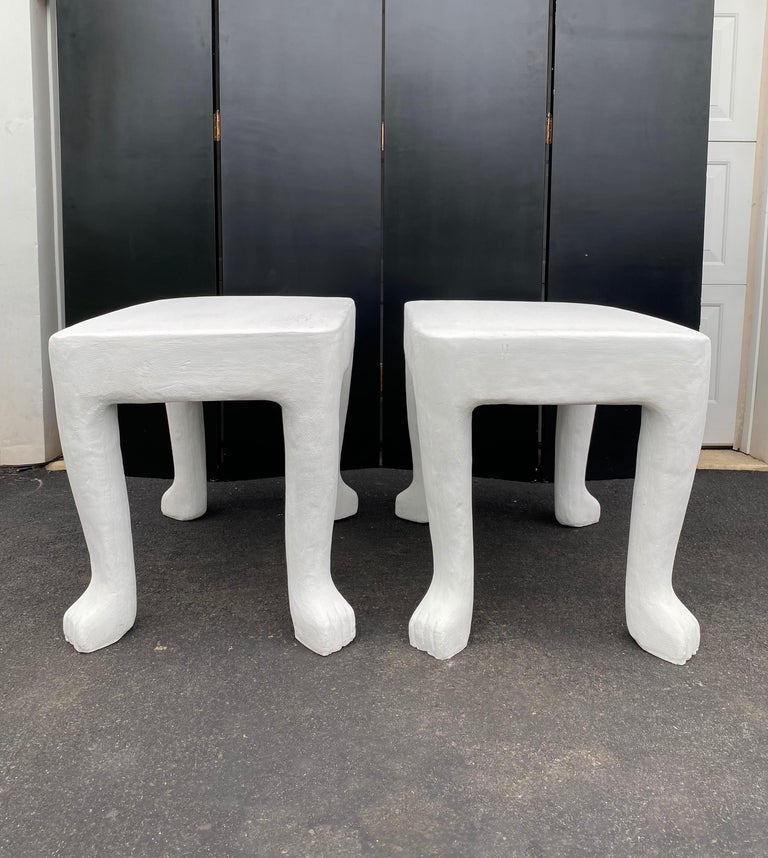 Pair of iconic John Dickinson footed end side tables. These early 2000s sculptural anthropomorphic tables are made of glass-fiber reinforced concrete in original plaster chalk white matte finish.   These authentic statement pieces are artfully cast