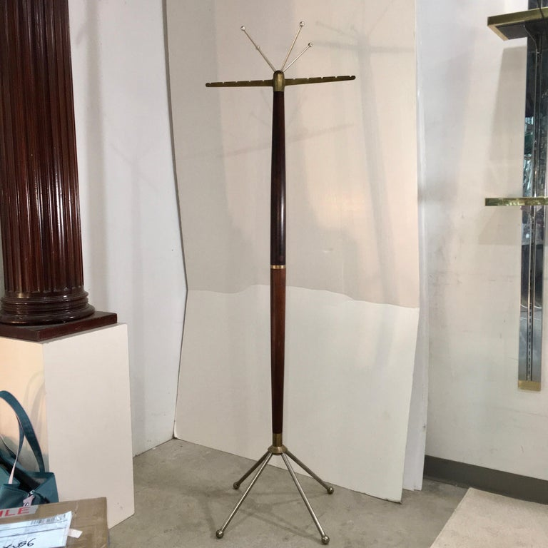 Stylish and sculptural 1950s Italian standing coat rack in tapered walnut with gilt metal accents. Includes four wood coat hangers from the Grand Hotel Bristol di Merano.