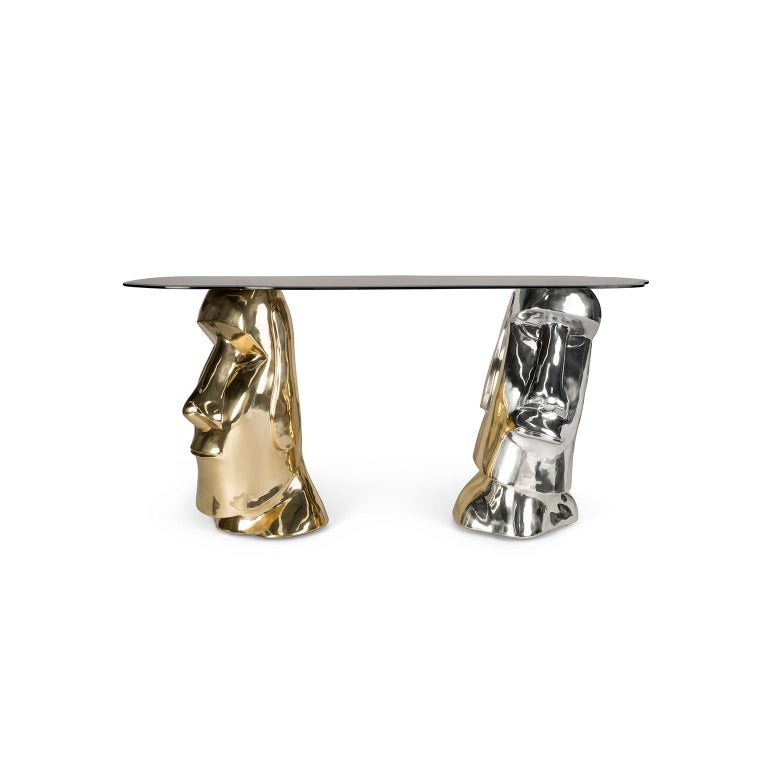 """1. Product description:  The """"Moai"""" console table is made of polished and nickel-plated brass cast and its top is a bronze tempered glass piece. This console table inspired by the colossal stone statues located on the Easter Island goes through a"""