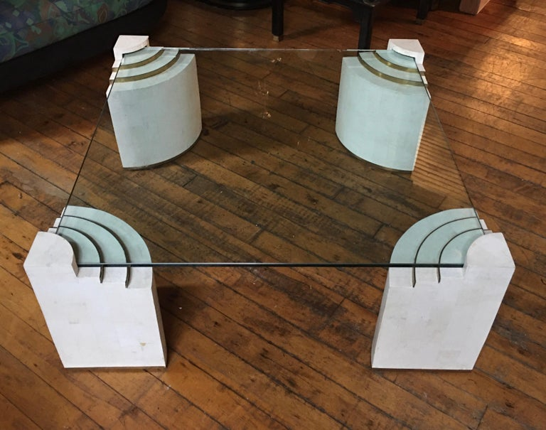 Stunning Mid-Century Modern tessellated stone coffee table designed by Robert Marcius for Casa Bique. Large square glass top is supported by four sculptural tessellated stone legs with brass band/trim detailing. In the style of Maitland Smith and in