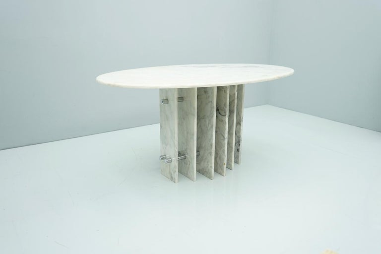 Beautiful oval dining table in withe / grey Carrara marble. Two columns with single marble discs in different wide, screwed with a chrome tube.