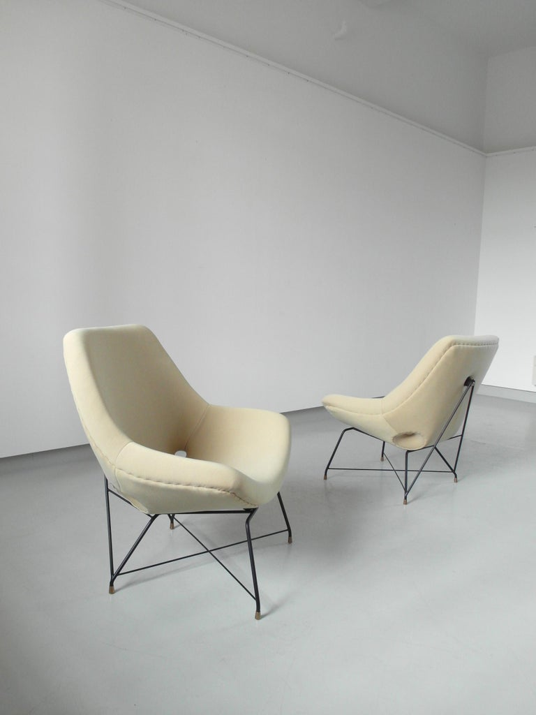 Sculptural pair of lounge chairs metal and fabric, designed by Augusto Bozzi for Saporiti, Italy, 1954. The delicately designed frame is made of black coated metal with elegant brass details. The shell is wide and sculptural and very comfortable.