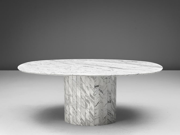 Oval dining table, Carrara marble, Germany, 1970s  This archetypical pedestal table is a skillful example of Postmodern design. The table is executed in white Carrara marble with grey lines. The oval table features no joints or clamps and is