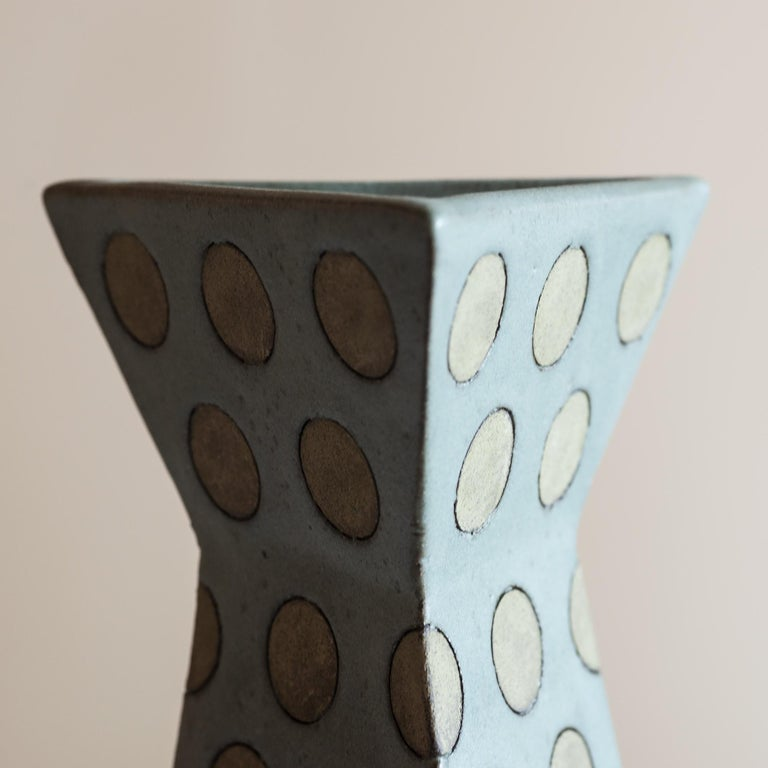 Triangular stoneware vase with polka dots in muted grey-green tones.